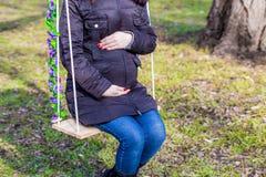 接触她的腹部用手的美丽的孕妇 库存图片