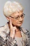 接触她的面孔的一个老妇人,担心。 免版税库存照片