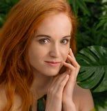 接触她的面孔,绿色背景的年轻红头发人妇女 库存照片
