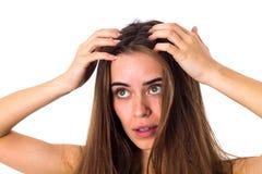 接触她的头发根的妇女 图库摄影