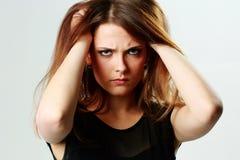 接触她的头的年轻恼怒的妇女 免版税库存照片