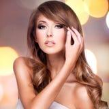 接触她美丽的头发的一名可爱的妇女的照片 免版税图库摄影