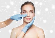 接触妇女面孔的外科医生或美容师手 图库摄影