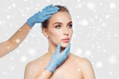 接触妇女面孔的外科医生或美容师手 库存图片