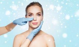 接触妇女面孔的外科医生或美容师手 免版税库存图片