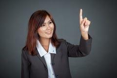 接触屏幕和微笑的亚裔女商人 免版税图库摄影