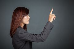 接触屏幕的亚裔女商人侧视图  免版税库存照片