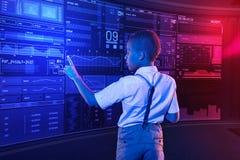 接触屏幕的镇静男孩,当检查信息时 库存照片