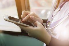 接触工作的妇女医生软的焦点黑屏在咨询的现代智能手机在工作场所医院 库存图片