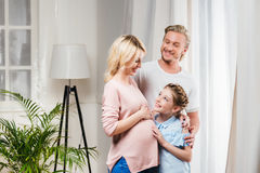 接触怀孕的母亲的微笑的女孩鼓起与近父亲由在家 免版税库存图片