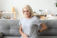 接触感觉的担心的哀伤的老妇人背部疼痛 库存照片
