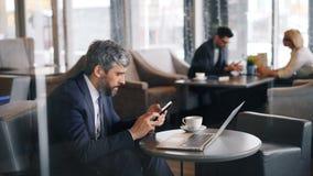 接触智能手机屏幕的灰发的商人使用在咖啡馆的小配件 影视素材