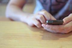 接触智能手机的人手 免版税库存图片