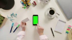 接触有一个绿色屏幕的手指一个智能手机 免版税图库摄影