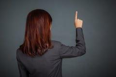 接触有她的手指的亚裔女商人屏幕 免版税库存图片