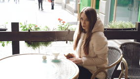 接触杯子的俏丽的女孩,使用在咖啡馆的电话,当咖啡蒸4K 股票视频