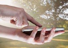 接触电话的手反对有火光的模糊的公园 免版税图库摄影