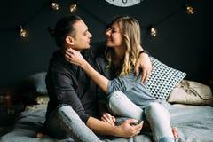 接触的男朋友和girfriend坐与灰色毯子和枕头的床 有光的舒适室 免版税库存图片