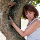 接触福利的性感的老化妇女一棵树 免版税图库摄影
