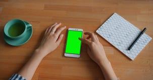 接触绿色智能手机屏幕的人的手的慢动作与小配件一起使用 股票视频