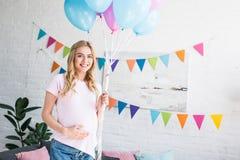 接触腹部和拿着捆绑气球的美丽的孕妇 图库摄影