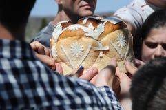 接触装饰的面包,正统复活节的庆祝的人的手 免版税库存图片
