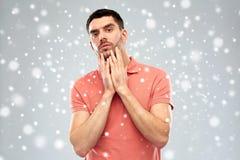 接触他的在雪背景的年轻人面孔 图库摄影