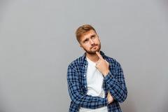 接触他的胡子用手的一个沉思人的画象 免版税库存照片