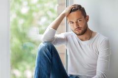 接触他的头发的英俊的体贴的人放松在窗口sil 图库摄影