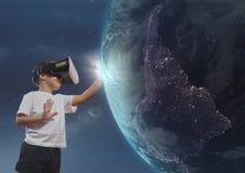 接触3D行星的VR耳机的男孩反对天空背景 免版税库存图片