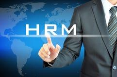 接触HRM (人力调配)标志的商人手 免版税库存照片