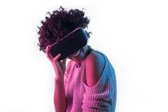 接触VR耳机的快乐的女孩 免版税图库摄影