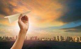 接近为伸手可及的距离的手和纸飞机对都市天空 免版税库存照片
