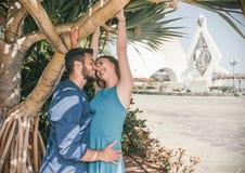接近室外的亲吻的爱的年轻夫妇-浪漫愉快的恋人有爱一个逗人喜爱的故事在他们的蜜月的假期 免版税库存照片