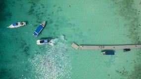 接近对在清楚的蓝色海的跳船的速度小船顶视图 图库摄影