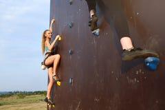 接近对在速度上升的竞争速度轨道的完成的点的两个年轻登山人底视图  免版税库存图片
