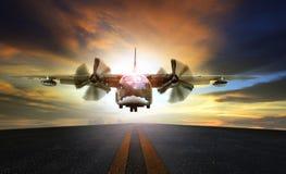 接近对登陆的老军用飞机在机场跑道 库存图片