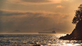 接近岸的大货船在日落的雨云 免版税库存照片