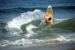 接近岸的年轻男性冲浪者 免版税库存照片