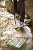 接近攀登山的墙壁的一块垂直的白色石头的一些绿色步帮助对有杆的徒步旅行者的保存 库存图片