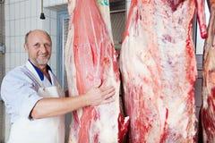 接近母牛尸体的愉快的屠户 免版税库存照片