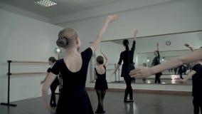 接近由老师复制舞蹈运动在芭蕾演播室小芭蕾舞女演员的后面  股票录像