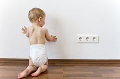 接近电力输出的婴孩 库存图片