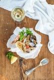 接近的免费平底锅意大利面食海鲜 有蛤蜊和虾的意粉在碗,杯在土气木背景的白葡萄酒 免版税库存照片