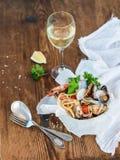 接近的免费平底锅意大利面食海鲜 有蛤蜊和虾的意粉在碗,杯在土气木背景的白葡萄酒 免版税库存图片
