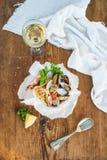 接近的免费平底锅意大利面食海鲜 有蛤蜊和虾的意粉在碗,杯在土气木背景的白葡萄酒 库存图片