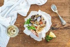 接近的免费平底锅意大利面食海鲜 有蛤蜊和虾的意粉在碗,杯白葡萄酒 免版税库存图片