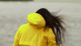 接近的后面观点的红色妇女头发招标运动在天空中在慢动作 走在沙滩的妇女 r 股票录像