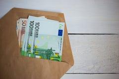 接近的捆绑金钱在信封的欧元钞票在木桌上 库存照片