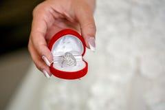 接近的新娘在手边拿着美好的婚礼或定婚戒指 免版税图库摄影